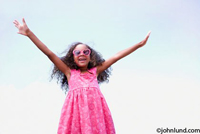Happy black girl in pink heart shaped sunglasses with arms outstretched and wearing a pink print dress with a lot of curly hair.